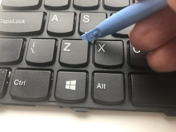Insert an opening tool beneath one of the top corners of the key you wish to remove and angle it upwads until you feel it unclip.