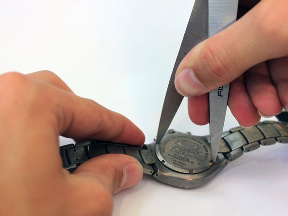 Fit the blades of a pair of scissors into the grooves of the screw back.