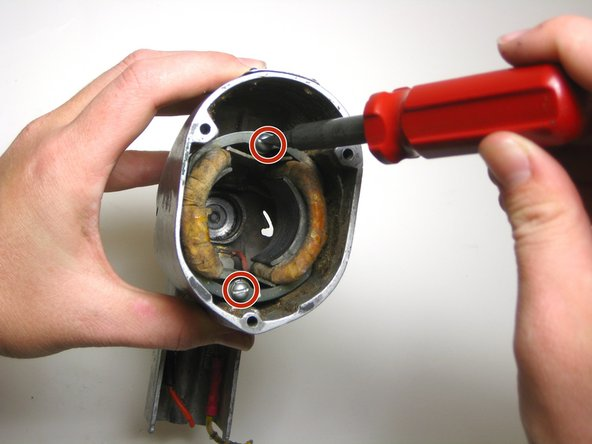 """Remove the two 1"""" flathead screws located at the top and bottom of the motor housing."""