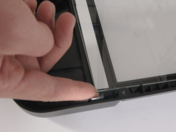 Once the screw has been taken out, lift the glass covering from the bottom left corner as shown.