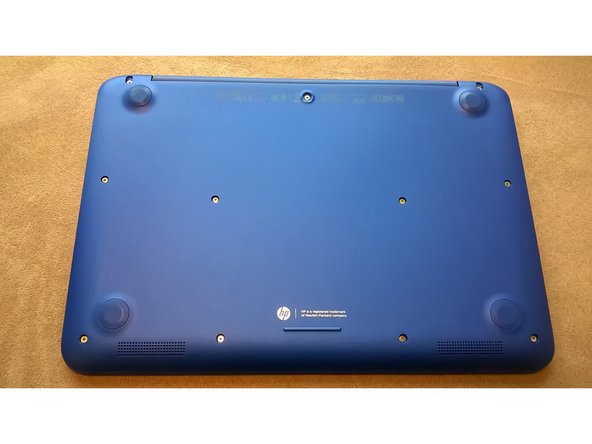Flip your laptop over. There are four pads that you need to remove to access the screws. Remove the center pad first as shown in the picture.