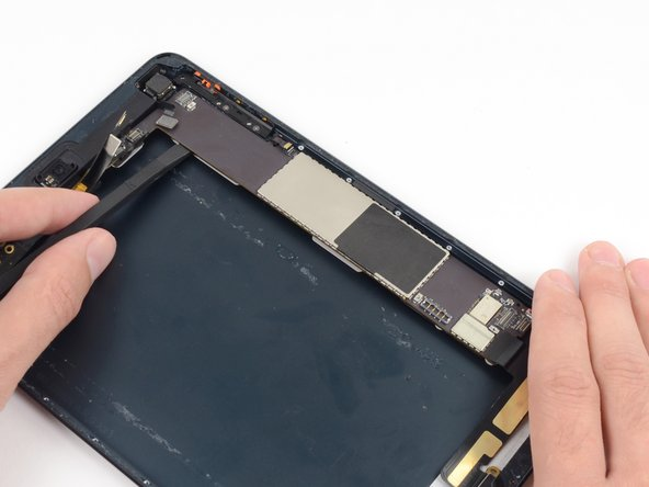 Insert the spudger further under the logic board and slide along its length to detach the last of the adhesive.