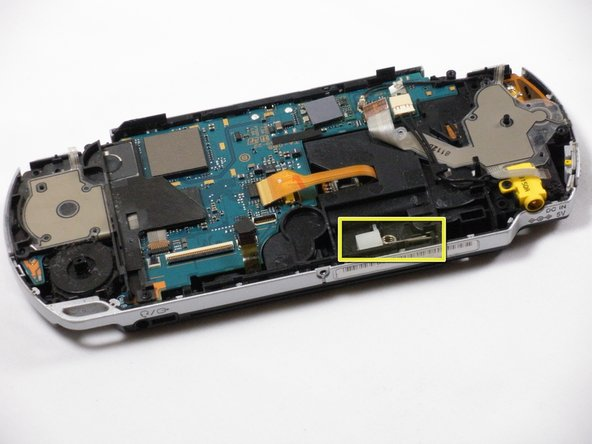 With the front side of the PSP facing you, locate small white plastic box with metal spring attached.