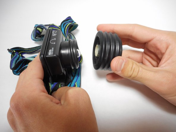 Remove the extended lens piece by firmly pulling the lens piece away from the battery housing. Take care to properly dispose of the damaged lens piece.