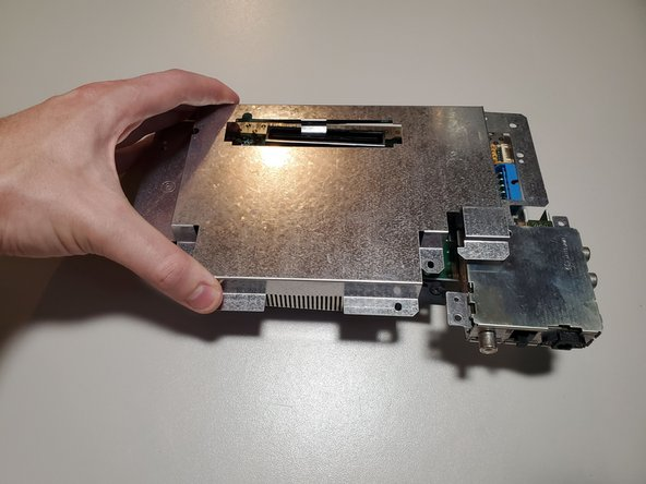 The bottom RF shield is held on by tension around the expansion port. Lift the shield up and away from the motherboard.