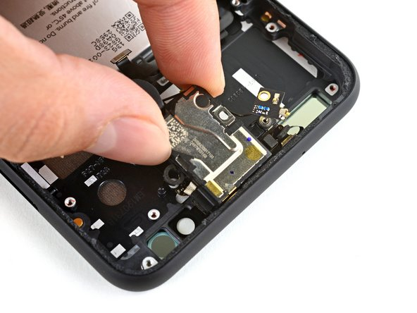 Pull the earpiece speaker away from the light adhesive holding it to the phone's top frame.