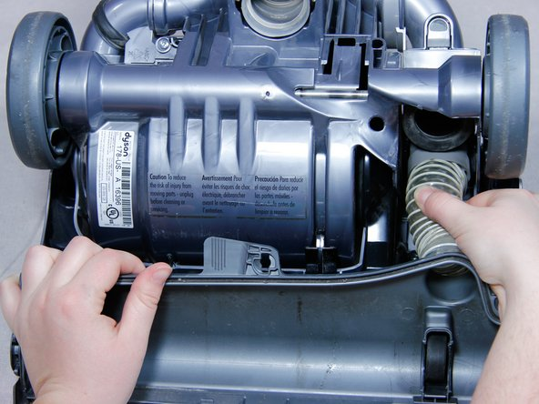 Pull the clear hose out of the gasket on the right side of the vacuum under the axle.