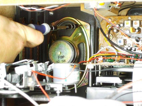 Using your Phillips head screwdriver, remove the 4 brass speaker screws.