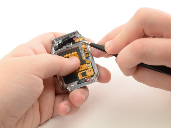Use tweezers to grab the orange connector that is attached to side the home button assembly and lift to remove it from its adhesive.