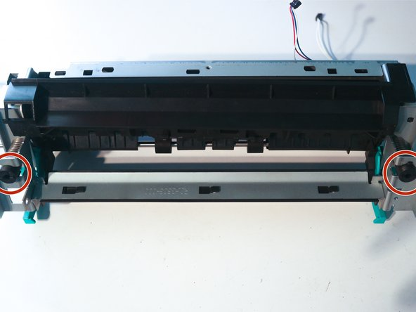 Remove the large springs at each side of the fuser by pushing in on the plastic inserts.