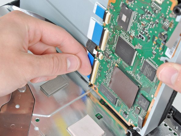 Use your fingernail to flip up the retaining flap on the Blu-ray ribbon cable socket.