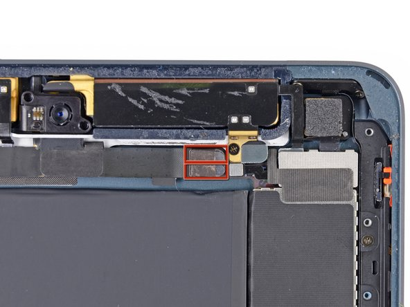 The front-facing camera cable connector is secured with pieces of tape that wrap up around the sides of the cable and are fastened to two small metal plates.