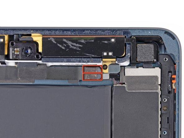 Le connecteur de la nappe de la caméra frontale est fixé avec des morceaux de ruban qui s'enroulent autour des côtés de la nappe et sont fixés à deux petites plaques métalliques.