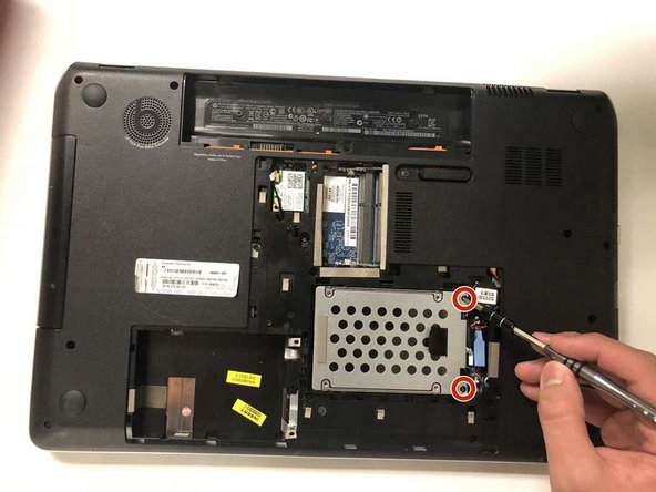 Remove the two Phillips #00 screws holding in the hard drive.