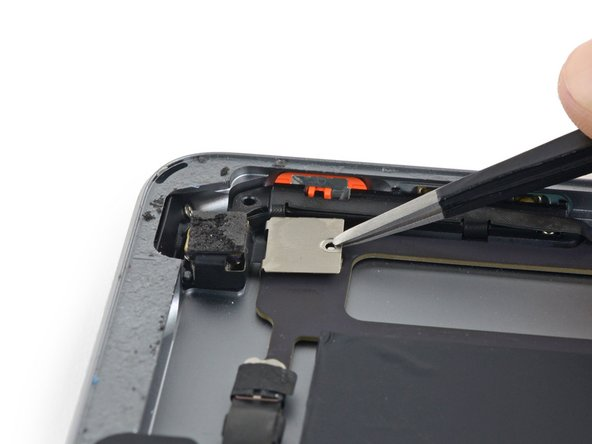The rear-facing camera cable bracket is clipped over the edge of the logic board and cannot be simply lifted straight off.
