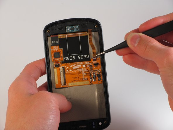 Using the tweezers, carefully pull the gold display cable to remove it from its attachment.