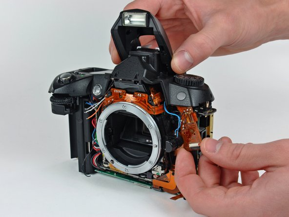 Carefully lift the top cover near the mode dial as you pull the mode dial ribbon cable away from the lens base.