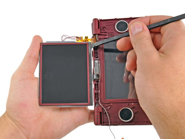 Insert the flat end of a spudger underneath the adhesive strip that secures the front screen to the upper LCD.