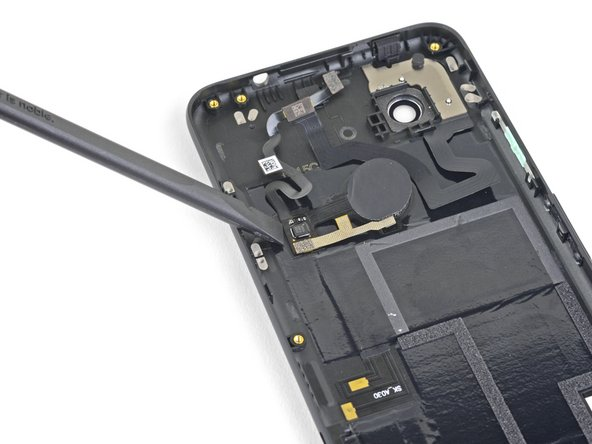 Use the flat end of a spudger to pry up the fingerprint sensor cables adhered to the inside of the back cover.