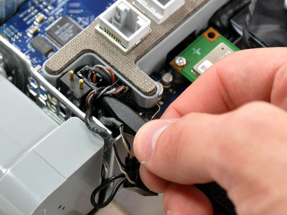 Use the tip of a spudger to slightly lift the lower fan cable and microphone cable.