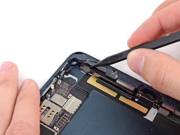 With the tip of a spudger, peel up the larger piece of tape covering both antenna cables near the bottom of the rear case.