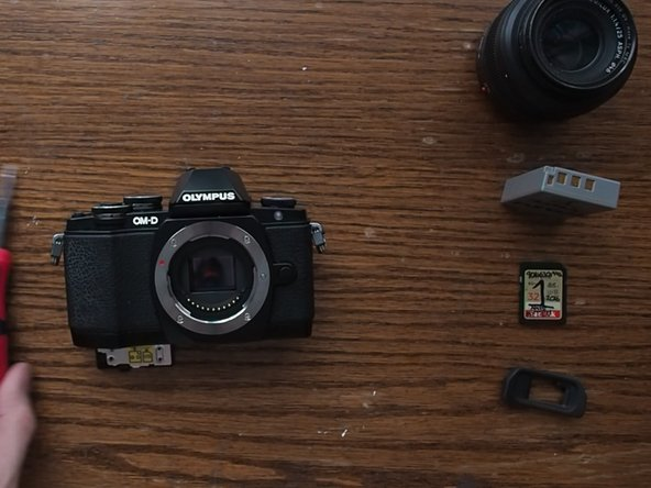 Remove the lens, battery, SD Card, and EVF eye cup
