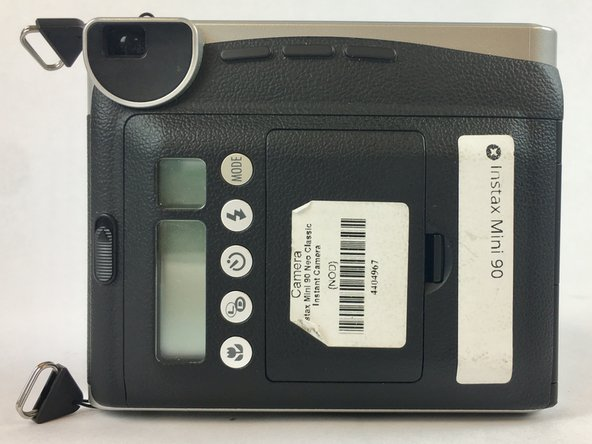 The battery compartment can be found on the backside of the camera. Pinpoint this compartment and focus on the right edge of the compartment gate to find the opening latch.