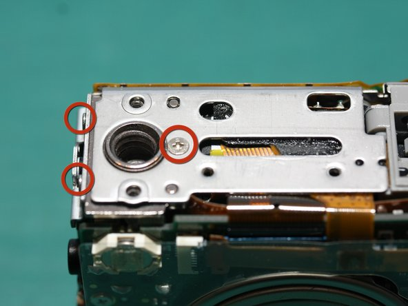 Remove the screw on the bottom plate. While we're at it, there are 2 screws on the side near here (2 circles at left). They hold the tripod socket to the side frame.