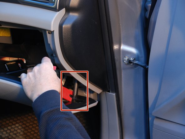 Unhook the glovebox retention arm from the side of the glovebox by squeezing the clip together with your fingertips, and prying the arm off the lower connection point only.