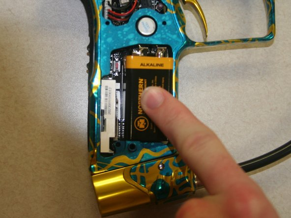 Push new battery into right side of grip, inserting the bottom first.