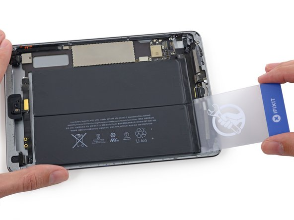 Remove the plastic card and insert it under the battery cell nearest the edge of the case.