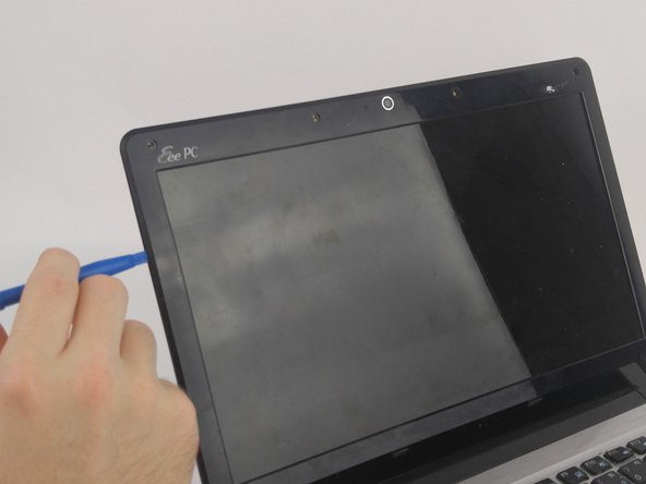 Using the plastic opening tool, separate the over from the netbook.