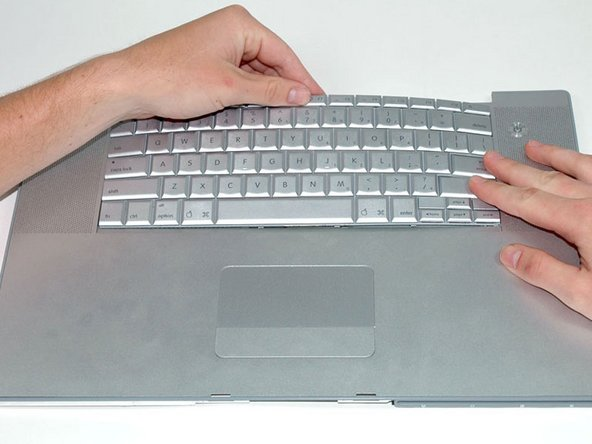 To replace the keyboard, first slide the bottom tabs in, then bow the keyboard out and slide in first the tabs on the right side of the keyboard and then the tabs on the left side.