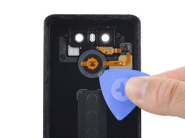 Slide an opening pick between the rear button membrane and the rear case.