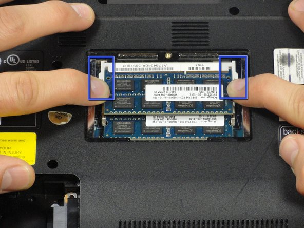 Pull the two retaining arms away from the center of the RAM chip.