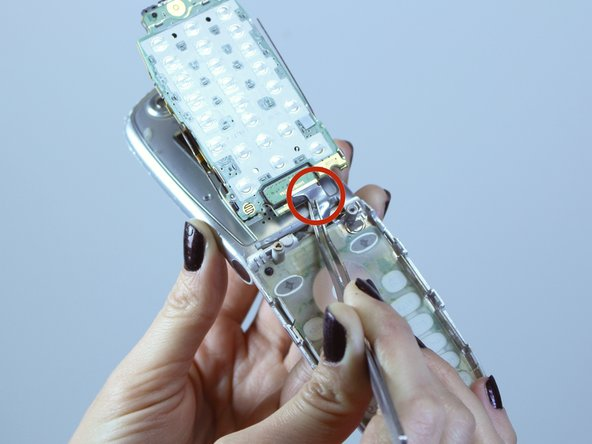 Using tweezers, pull on the silver flex ribbon to disconnect it from the motherboard.