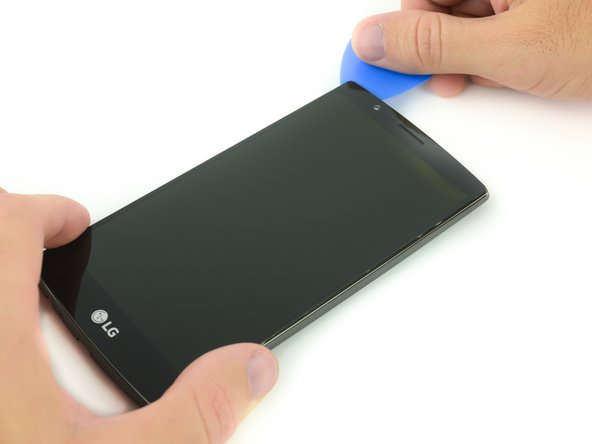 Insert a plastic opening pick into the gap between the screen and the plastic housing.