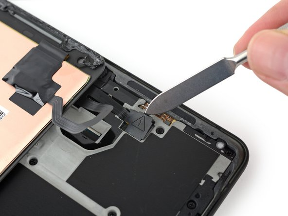 We'll have to untether the display before going any further. Its two cables are secured by plastic plugs in the midframe, and they only come out with some encouragement from a hefty pry tool.