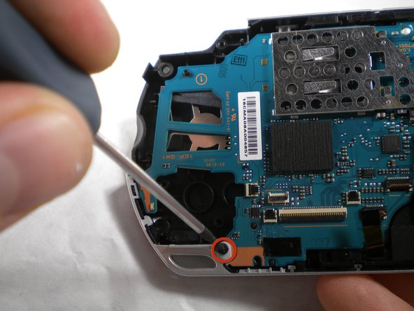 Use a Phillips #00 screwdriver to remove the bottom left screw attached to the PSP