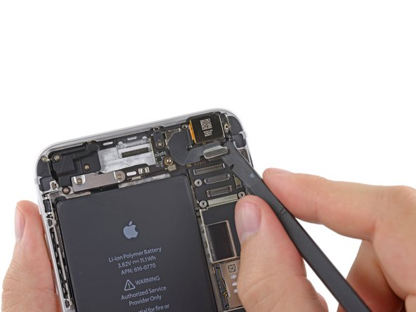 Use the flat end of a spudger to disconnect the rear-facing camera connector from its socket on the logic board.