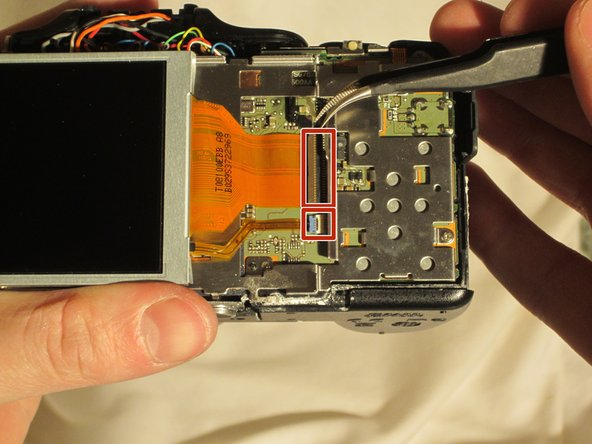 Using the tweezers, lift the hinges connecting the two ribbon wires to the camera.