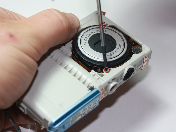 Using the Phillips #00 Screwdriver, remove the two screws holding the lens in place.