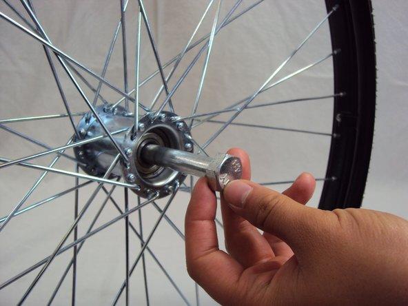 Insert the axle bolt into center of rear wheel.