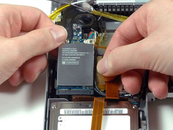Peel back the orange tape on the right side of the Airport Extreme card.