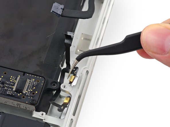 Pull the dual microphone cable assembly up and toward the logic board recess to remove it from the upper case.