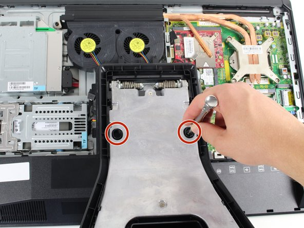 Use a Torx T15 driver and stick it through the holes on the stand in order to remove the two 12mm screws on the back of the main unit.