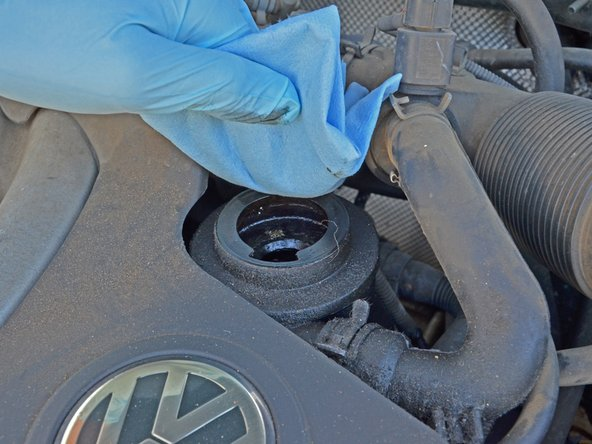 Wipe down the area around the filler cap with a rag or towel to remove any oil or debris.