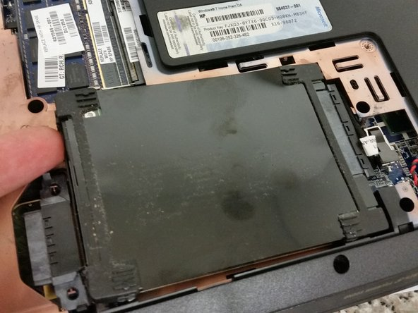 Simply pull the hard drive upwards and out, there are no screws. Be sure to disconnect the connector from the board.