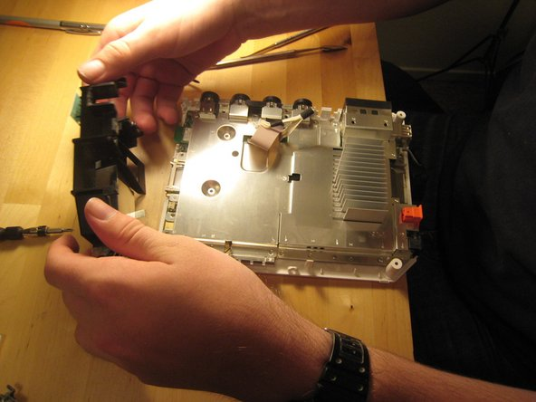 With the black plastic covers off, we can see all the screw holes. Most of the screws are out by now, but once the rest of them are out, you can lift off the logic board cover.