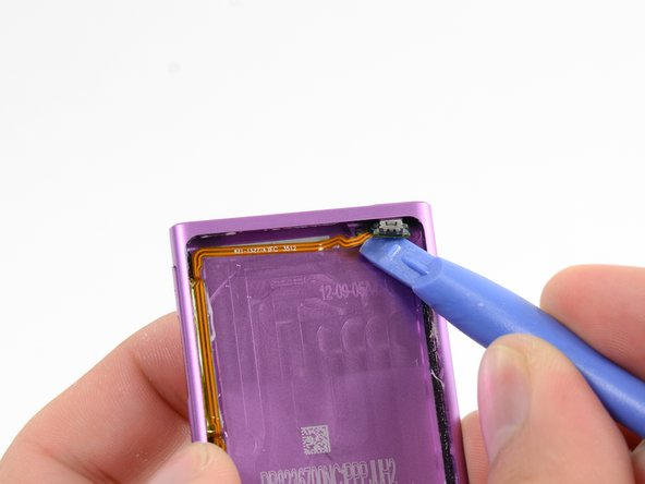 Insert a plastic opening tool under the sleep button, and gently pry upwards to free it from its adhesive.